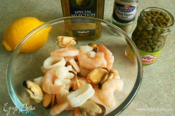 Морепродукты разморозить, смешать с перцами, каперсами и петрушкой. Взбить вилкой в миске все компоненты заправки и полить салат.
