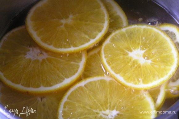 Приготовить декор-начинку. Вскипятить воду, добавить сахар и перемешать до растворения, добавить нарезанные тонкими ломтиками апельсины, варить 10-12 минут.