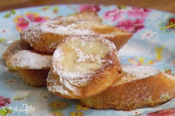 Обжаренный хлеб выложить на бумажное полотенце, чтобы убрать излишки жира, а затем полить кленовым сиропом и посыпать сахарной пудрой.