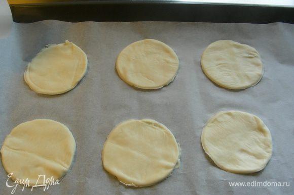 Песочное тесто раскатываем тонко и вырезаем небольшие кружочки (например, стаканом). Выкладываем их на противень на бумагу для выпечки.