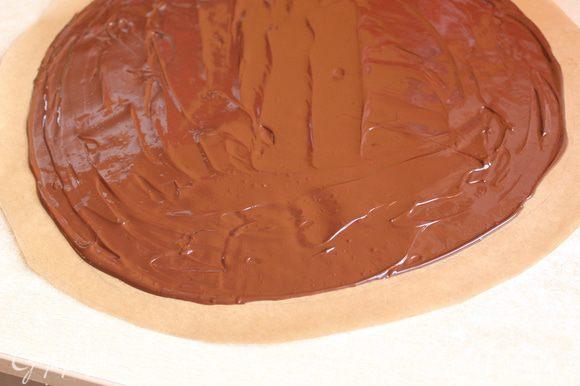Делаем наше покрывало... Берем бумагу и вырезаем круг диаметром 35 см. Внутри его отступаем на 2 см от края, рисуем еще один круг. На всякий случай я приложила свой круг к торту, проверила подойдет или нет... немного замазав конечно его... Теперь разогреваем шоколад на водяной бане, шоколад беру темный, 55% какао. Выливаем шоколад на бумагу и размазываем не доходя 2 см до края. Даем ему остыть на столе примерно минут 15.