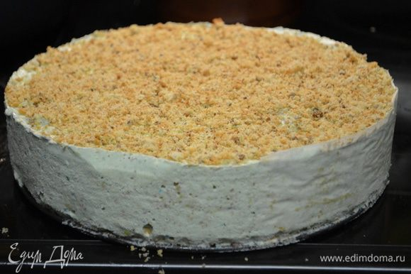 Взбить сливки с сахарной пудрой до мягких пиков.Достанем торт мороженое из морозильника как он станет твердым.Сверху распределим взбитые сливки. Я сняла форму,сняла бумагу по краю.Распределила крем по бокам, а затем выложила хрустящий миндаль слегка приминая к торту.