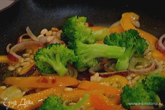 Разогреть в сковороде оливковое масло, немного обжарить лук и сладкий перец, затем добавить кедровые орехи и брокколи, перемешать, посолить, поперчить.