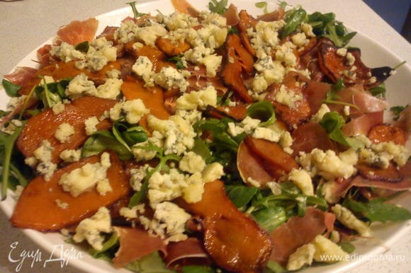 Добавить к листьям нарезанные помидоры, порвать руками хамон и перемешать. Сверху выложить тыкву и покрошить на нее сыр.