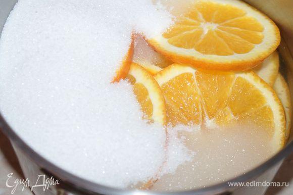 В кастрюлю выложить кружочки апельсинов, засыпать сахаром (350 г) и залить водой (400 мл). Поставить на огонь, довести до кипения и варить на среднем огне под крышкой 20 минут. Остудить. Сироп не выливать.