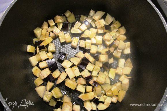 В кастрюле с плотным дном разогреть 80 мл оливкового масла, обжарить в нем порциями на сильном огне баклажаны, добавляя оливковое масло если необходимо.