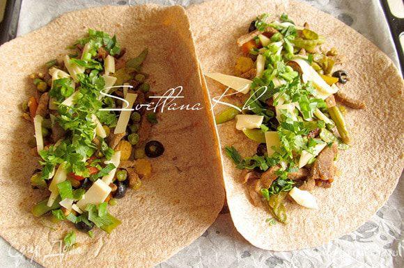 На лепешки выложить готовую смесь овощей с говядиной. Посыпать сыром, зеленью и луком. Выложить по 1 ч.л. сметаны и кетчупа.