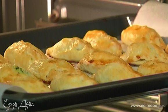 Противень выстелить бумагой для выпечки, выложить пирожки, смазать со всех сторон желтком с молоком и выпекать в разогретой духовке до готовности теста 20–25 минут. Подавать пирожки теплыми.