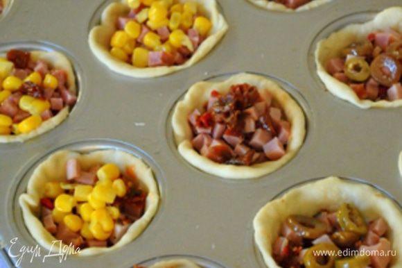 На дно тестяных формочек положить щедро томатный соус, сверху начинку.
