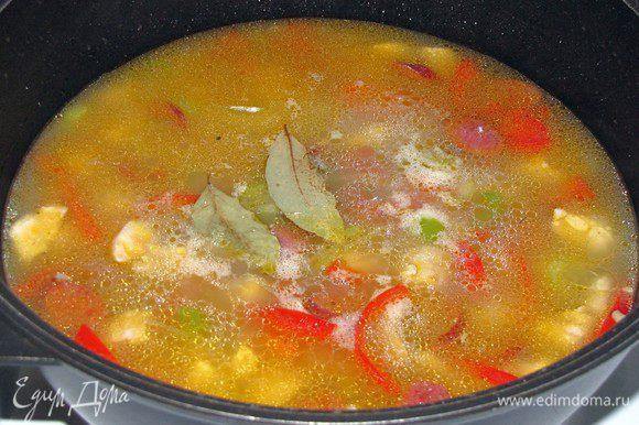 Влить куринный бульон, положить сверху лавровый лист. На сильном огне довести джамбалайю до кипения, после чего уменьшить огонь, накрыть крышкой и готовить 20 минут или меньше, до готовности риса.
