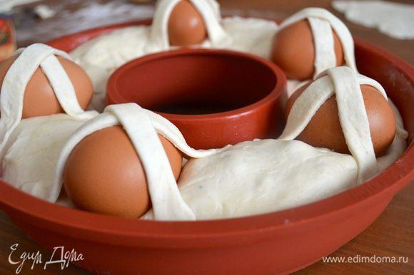 Закрепить наискосок этими полосочками теста выложенные по караваю яйца.