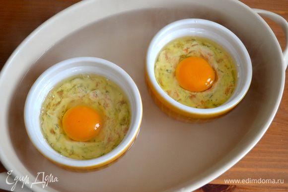 Взять глубокую форму, поставить в нее кокотницы и налить в форму кипяток, по уровню на половину высоты формочек с яйцами. Поставить в разогретую духовку на 15 минут.