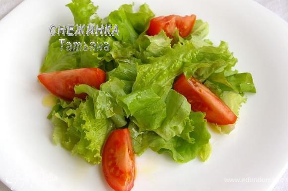 Пока пирожки запекаются, подготовим основу для салата. На порционную тарелку кладём салатные листья. Если салат крупный, рвём его руками. Половинку помидора нарезаем дольками. Сбрызгиваем основу оливковым маслом.
