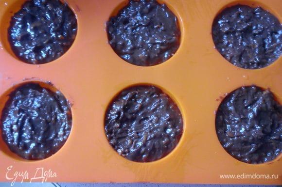 Смазать формы для кексов подсолнечным маслом и выложить тесто, заполняя их на 2/3. Выпекать в заранее разогретой до 180 С духовке 30 минут