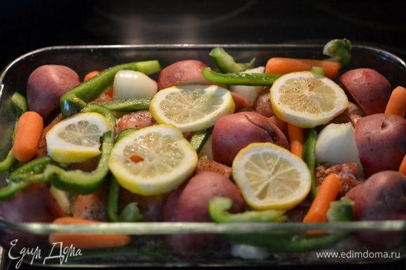 Поверх выложить овощи. Сверху лимон колечками. Прикрыть фольгой. Поставить в духовку на 45 - 55 мин.