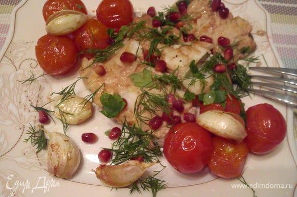 Выложить рыбку к помидорам и чесноку. Посыпать зернами граната и укропом.