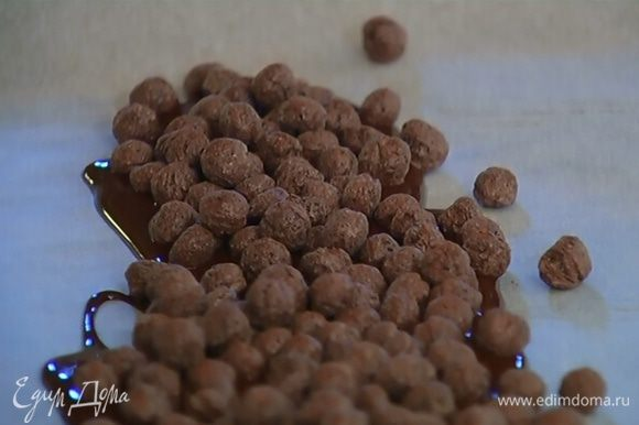 Расстелить на рабочей поверхности бумагу для выпечки, вылить на середину часть растопленного черного шоколада, насыпать на него шоколадные шарики и залить оставшимся черным шоколадом. Накрыть краями бумаги, постучать сверху толкушкой, чтобы немного раздробить шарики, и отправить шоколадную массу на 5 минут в морозильник.
