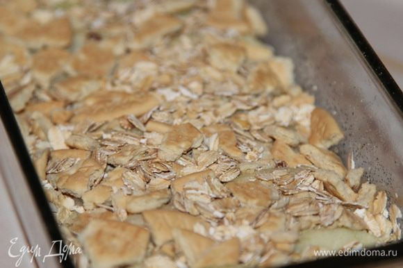 Следующим слоем снова крошим галетное печенье и добавляем еще овсяные хлопья не быстрого приготовления:
