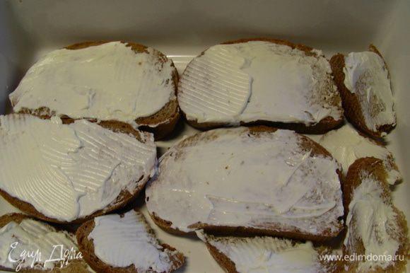 Хлеб смазываем с одной стороны сливочным сыром. В рецепте рекомендуют его разрезать на 4 части. Здесь все зависит от размера Вашей формы и от размера хлеба, который будете использовать. Подходящую форму слегка смазываем маслом и выкладываем туда слой хлеба сыром вверх (половину всего хлеба).