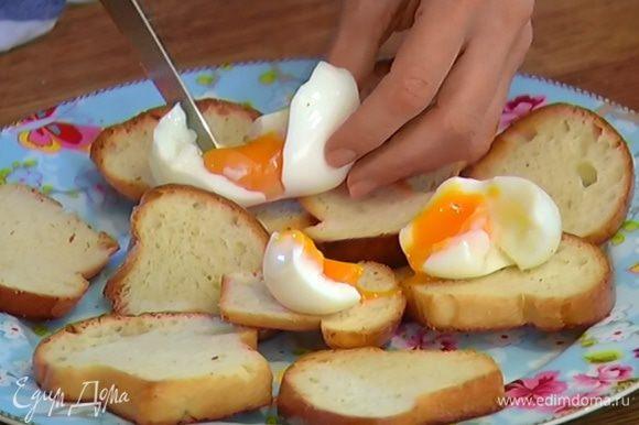 Яйца разломить руками и выложить на тосты, на яйца поместить ломтики семги, посыпать зеленым луком, сверху разложить спаржу.