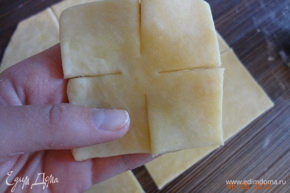 Отдохнувшее тесто раскатать в пласт (1-2 мм), вырезать квадрат, затем разрезать на маленькие квадратики (со стороной 10 см), сделать надрезы со всех сторон.