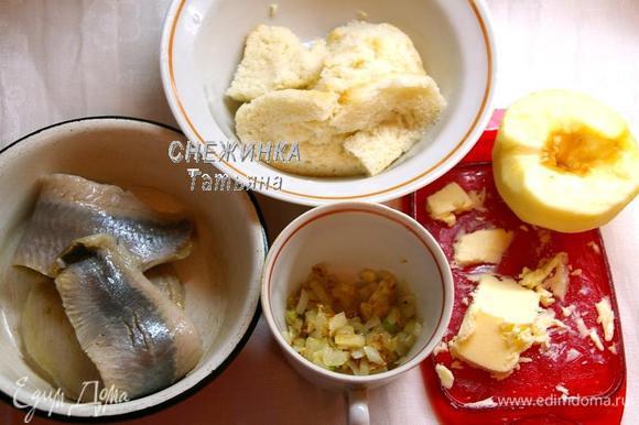 Подготовим все продукты для начинки. Селёдку режем крупными кусочками. Лук чистим, моем, нарезаем кубиком и обжариваем до мягкости на растительном масле. Белый хлеб заливаем небольшим количеством воды, чтобы он размок. Чистим яблоко от кожи и семян.