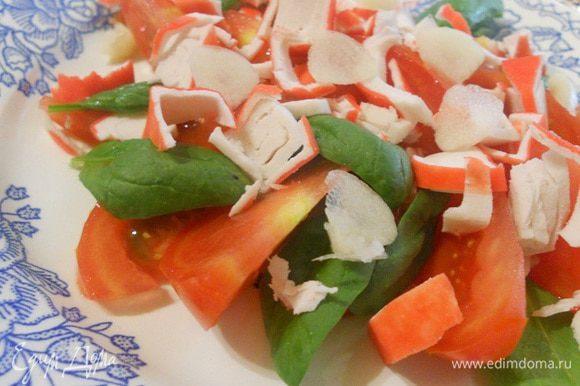 Помидор нарезать тонкими ломтиками, выложить на блюдо, между дольками выложить листья шпината, сверху накрошить крабовое мясо или палочку.