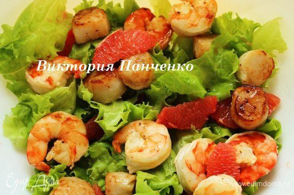 Салатные листья порвать руками, смешать с морепродуктами и грейпфрутом.