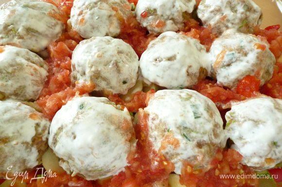 Из фарша формуем шарики и выкладываем их на овощи. Затем ложкой распределяем натертые томаты. Каждый мясной шарик смазать сметаной. Форму накрыть крышкой .Запекать в духовке 40 минут с момента закипания.