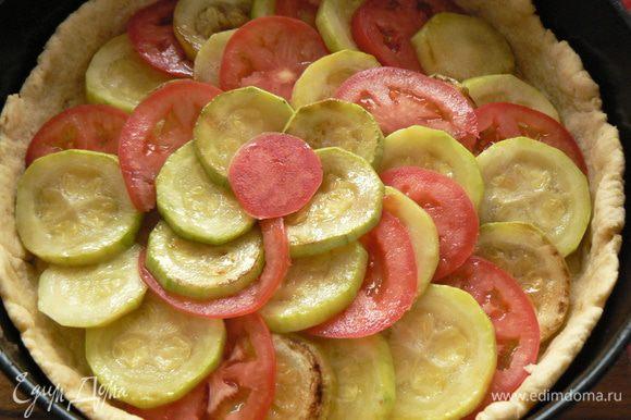 На тесто выкладываем кабачок, тонко порезанные помидоры