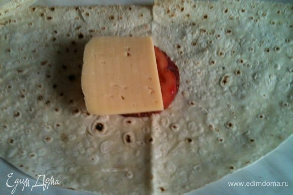 Кладем половинку лавашика на стол , кладем на серединку пластик колбаски, поверх пластик томата, посолить его, поперчить, поверх положить сыр.