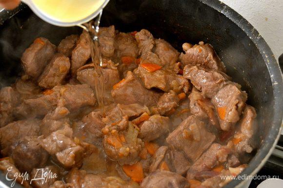 Влить в мясу белое сухое вино и продолжить тушить мясо, пока не выпарится алкоголь (около 10 минут).