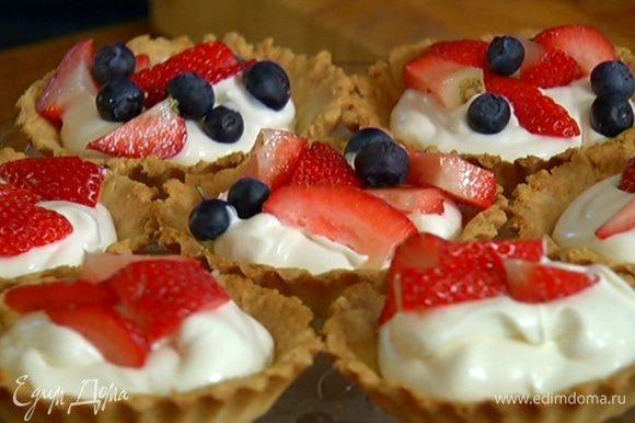 Готовые тарталетки остудить, наполнить взбитыми сливками, украсить ягодами и посыпать сахарной пудрой.