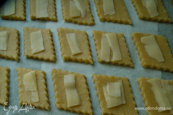 Тесто достаем из холодильника и даем ему согреться.Духовку разогреваем на 170-180С. Раскатываем пласт толщиной около 1 см. Нарезаем печенье произвольной формы, выкладываем его на противень, застеленный пекарской бумагой. На каждый кусочек кладем сырную стружку. Выпекаем печенье 12-15 минут до золотистого цвета.