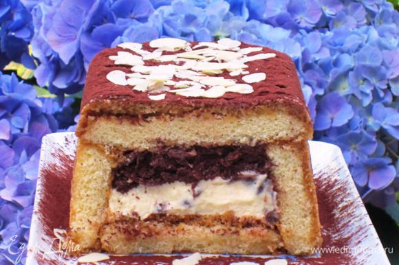 Поставить десерт в морозильную камеру на 3 часа. Посыпать какао и миндальными лепестками, нарезать на порции и подавать. Приятного аппетита:)