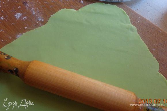 Раскатать часть зеленой мастики для нижнего коржа с таким расчетом, чтобы в центре осталось пространство для синей вставки.