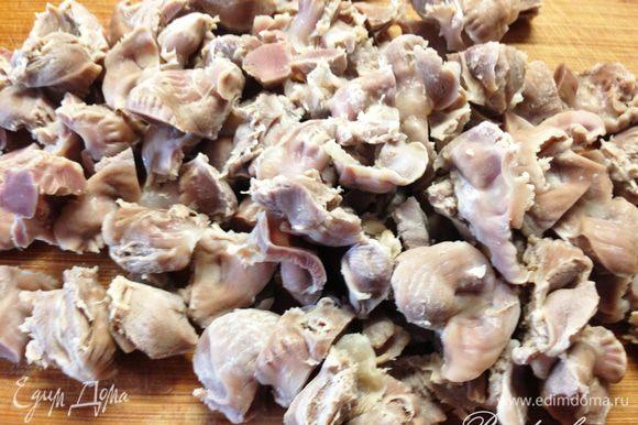 В кастрюлю налить около 2 литров воды, нарезать по вкусу куриные желудочки и довести до кипения. Первый бульон слить, желудочки промыть. Затем вернуть их в кастрюлю, залить водой и варить не менее 1 часа.