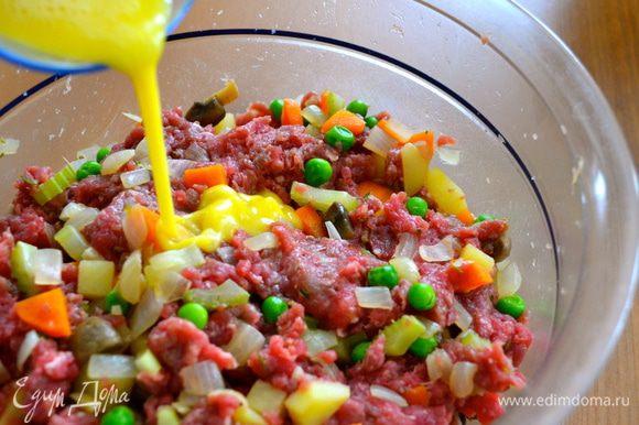 Разбить яйцо в стакане и взбить слегка вилкой. Половину яйца добавить в фарш с овощами. Еще раз все как следует перемешать.