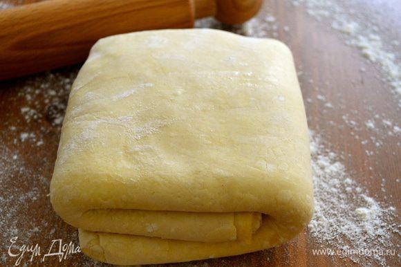 Рабочую поверхность стола присыпать мукой. Слоеное тесто раскатать в пласт размером примерно с кухонное полотенце.