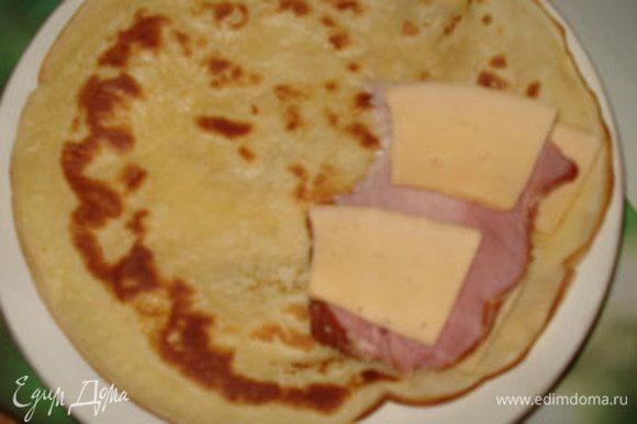 На одну половинку блина положить сыр, потом грудинку, сыр. Накрыть второй половинкой. Запечь в микроволновке до расплавления сыра (1 минута). Приготовить соус: смешать сметану и французскую горчицу в соотношении 1:1.