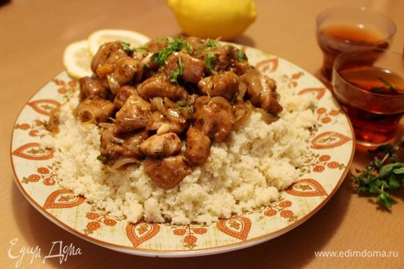 На большое блюдо горкой насыпать кускус, на кускус выложить курицу и полить всё соусом. Украсить блюдо кусочками лимона. Подавать с ароматными марокканскими лепёшками. Приятного аппетита!