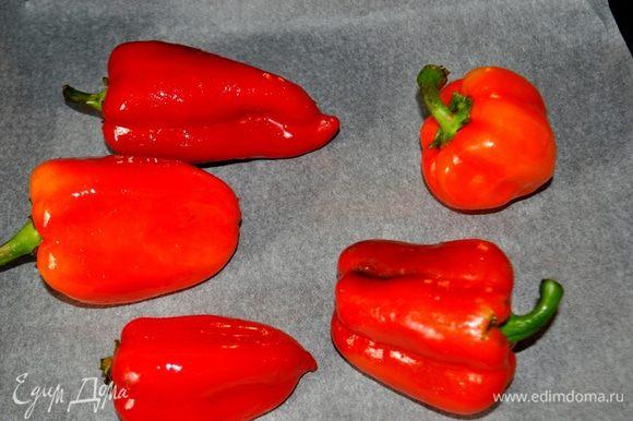 Перцы вымыть,вытереть на сухо,духовку разогреть до 200С, противень застелить бумагой для выпечки,перцы смазать оливковым или подсолнечным маслом, положить на противень перцы и запекать в духовке примерно 20 минут, пока кожица частично не почернеет. Во время запекания перцы один раз перевернуть