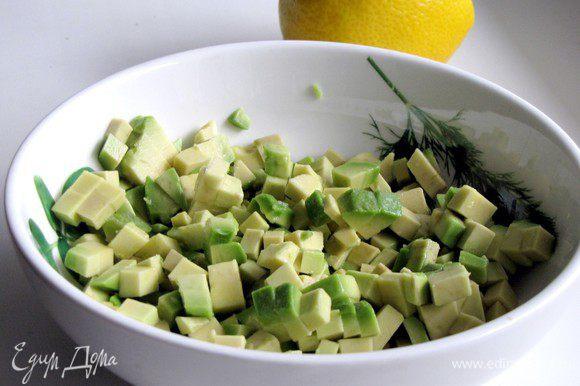 Авокадо разрежьте пополам, удалите косточку. Мякоть нарежьте кубиками, сбрызните лимонным соком.