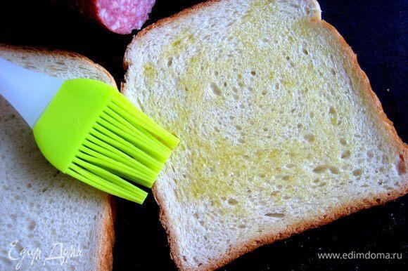 Нижний ломоть хлеба промазать оливковым маслом при помощи новенькой силиконовой кисточки...