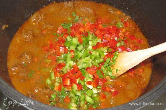 Зелень и перец добавить в казан, перемешать и тушить 2 минутки.