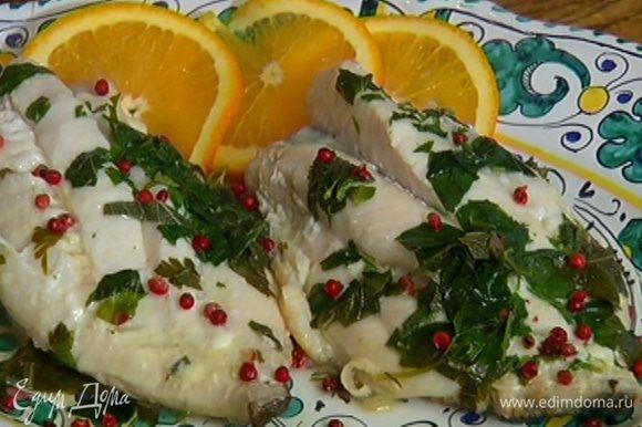 Готовую рыбу посыпать розовым перцем и подавать с кружками апельсина.