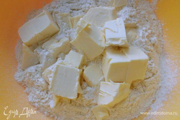 Сливочное масло нарезать кубиками, добавить к муке. Порубить масло с мукой в мелкую крошку.