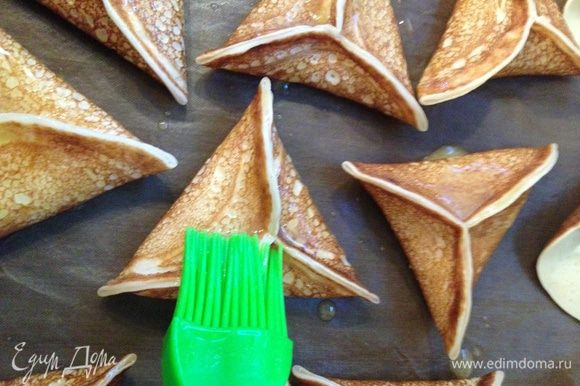 Блины перекладываем на застеленный бумагой для выпечки противень , смазываем их сверху растопленным сливочным маслом и ставим в разогретую до 180 С духовку на 5–6 минут.