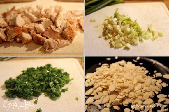 Куриное филе нарезать крупными кусочками, сельдерей-мелкими кубиками, зелёный лук-колечками. Виноград снять с грозди. Миндальные лепестки подсушить на сухой горячей сковороде. Сложить все ингредиенты в миску.