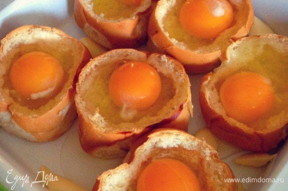 Вбиваем аккуратно в каждую булочку сырое яйцо...